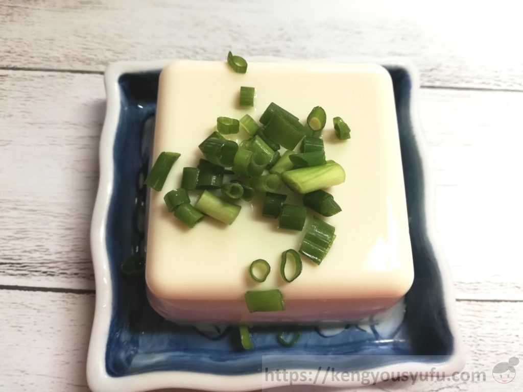 食材宅配コープデリで購入した国産素材「北海道産大豆絹(充填豆腐)」ネギを乗せた画像